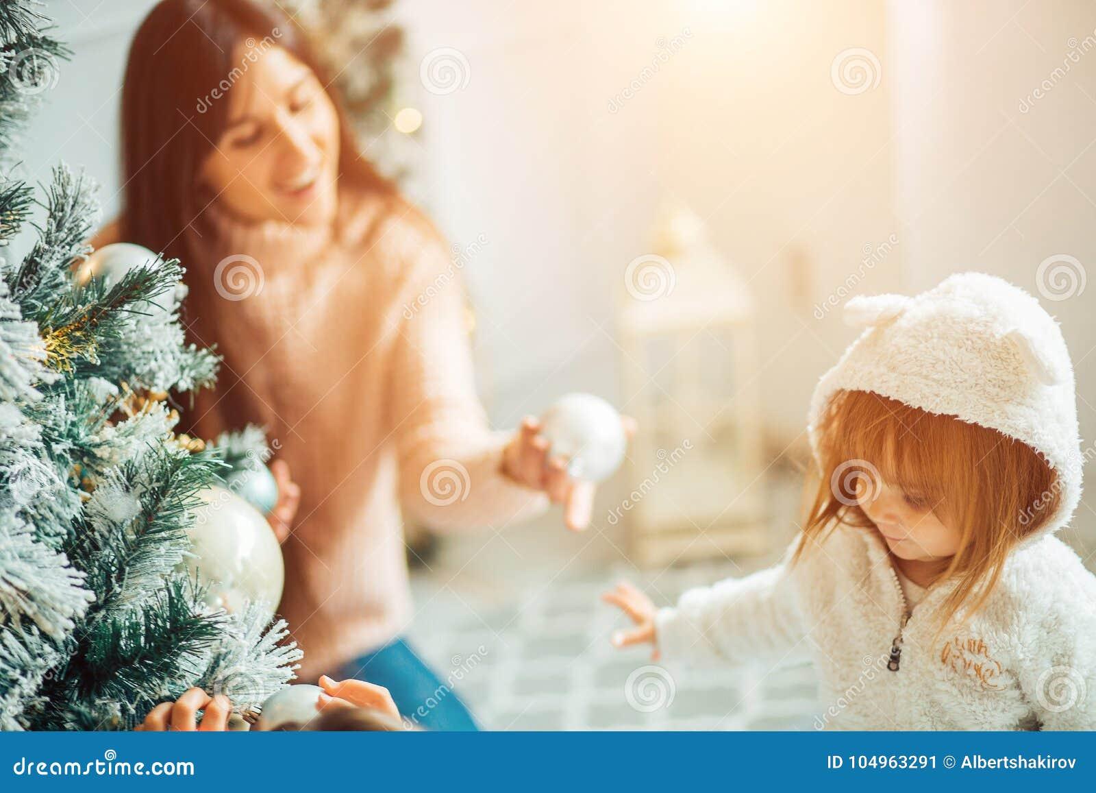 Мама и дочь украшают рождественскую елку внутри помещения