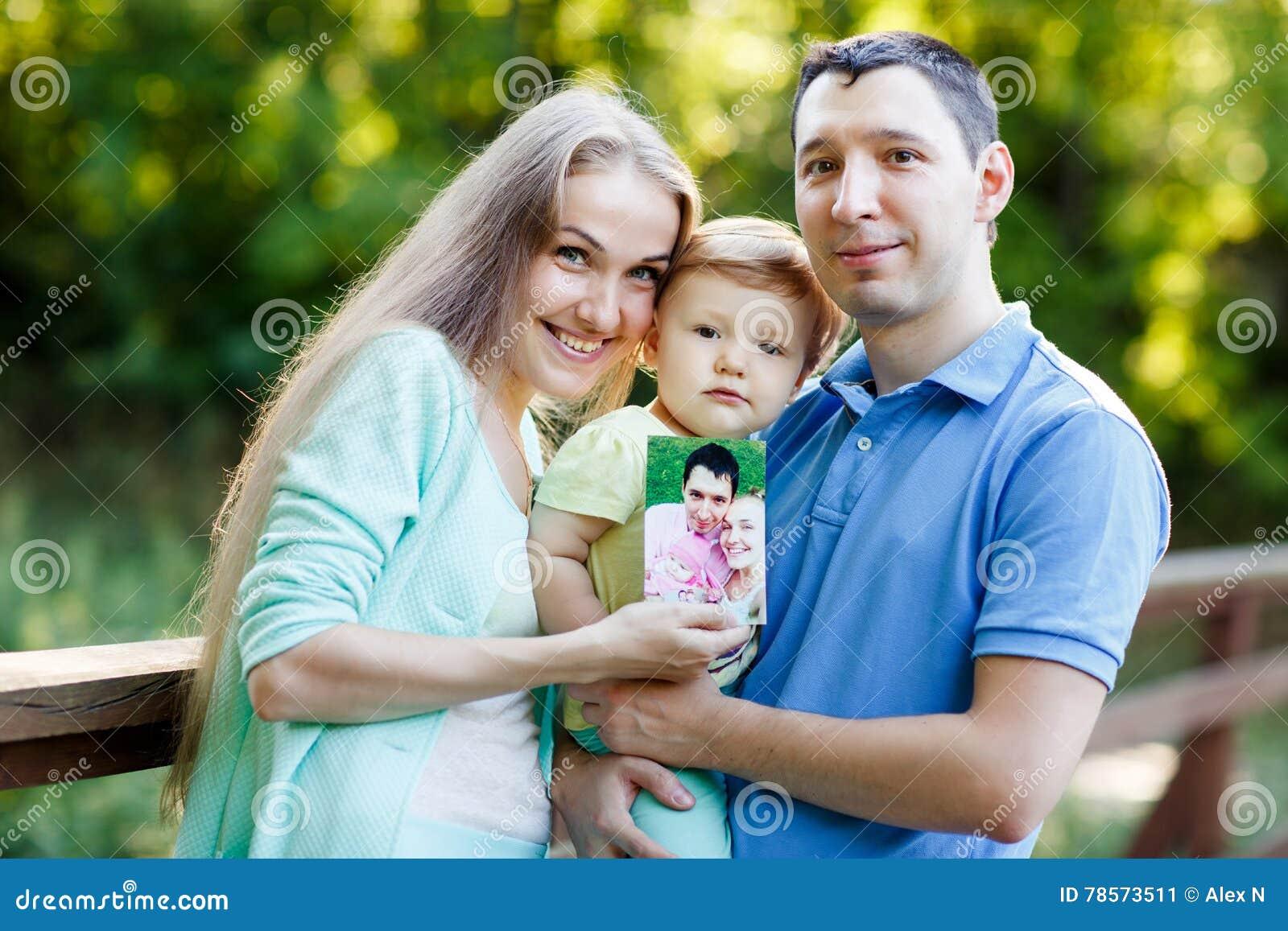 Мама, папа и маленькая девочка держа фото их жизней
