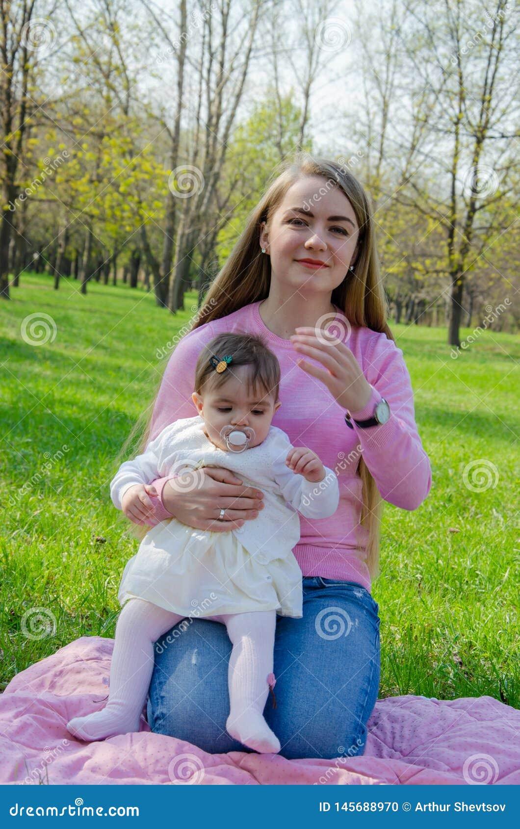 Мама с младенцем в ярких одеждах на розовой шотландке на зеленом праве Семья отдыхая в парке на теплый день