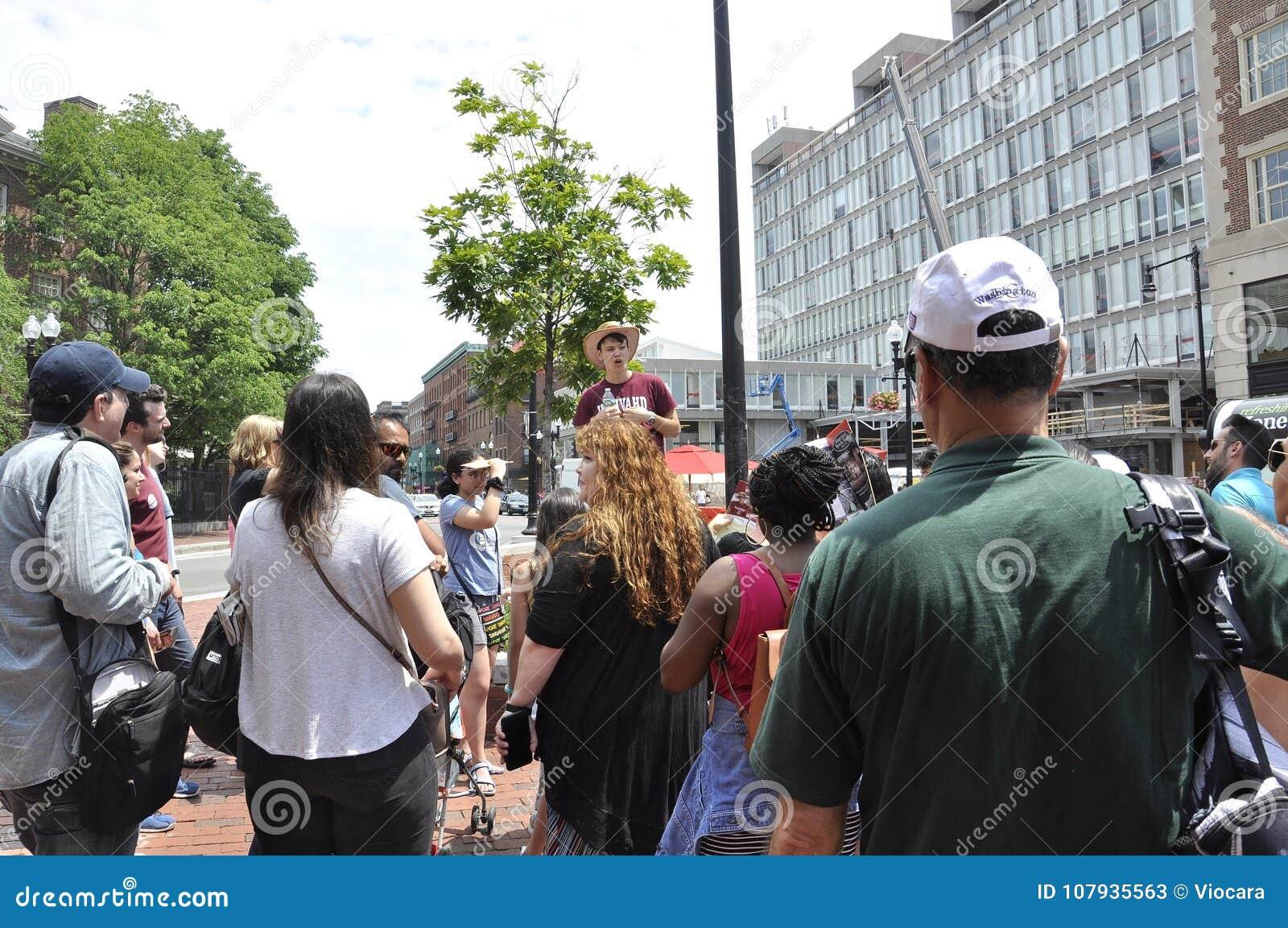 МАМЫ Кембриджа, 30-ое июня: Студент Гарварда направляет группу в квадрат Гарварда от Кембриджа городского в положении Massachuset