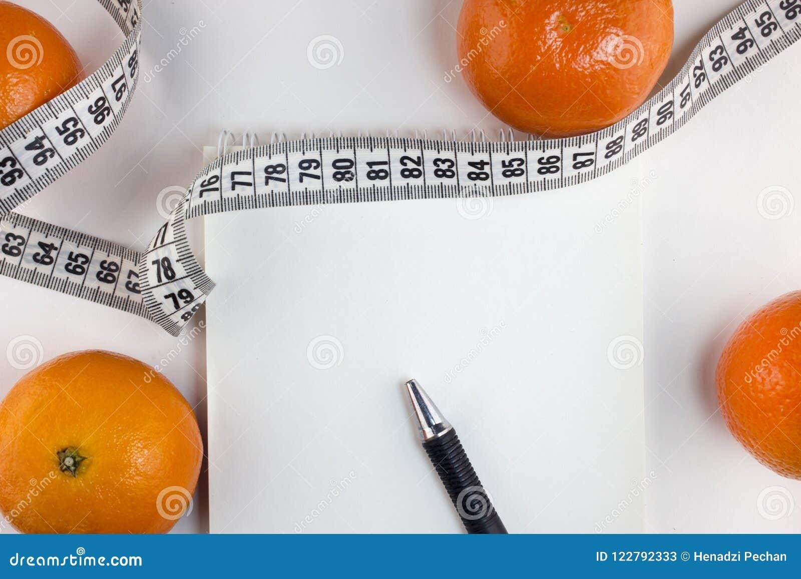 Мандарины, блокнот, лента сантиметра на белый dieting предпосылки