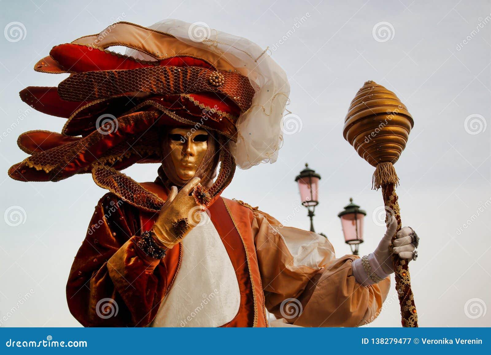 Маска и костюм красочной масленицы золото-бежев-коричневая на традиционном фестивале в Венеции, Италии