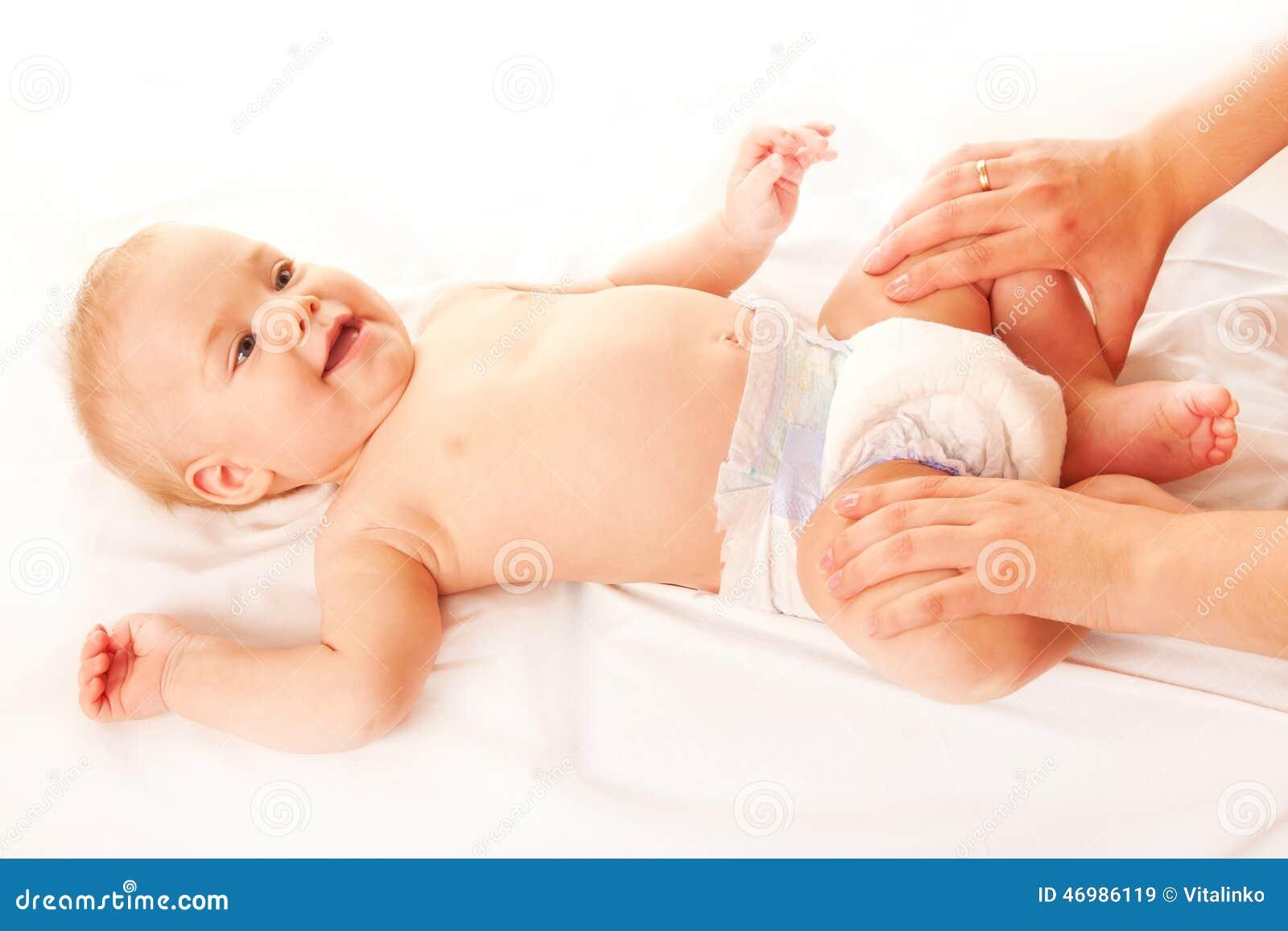 Массаж младенца Мать массажируя ноги ребенк