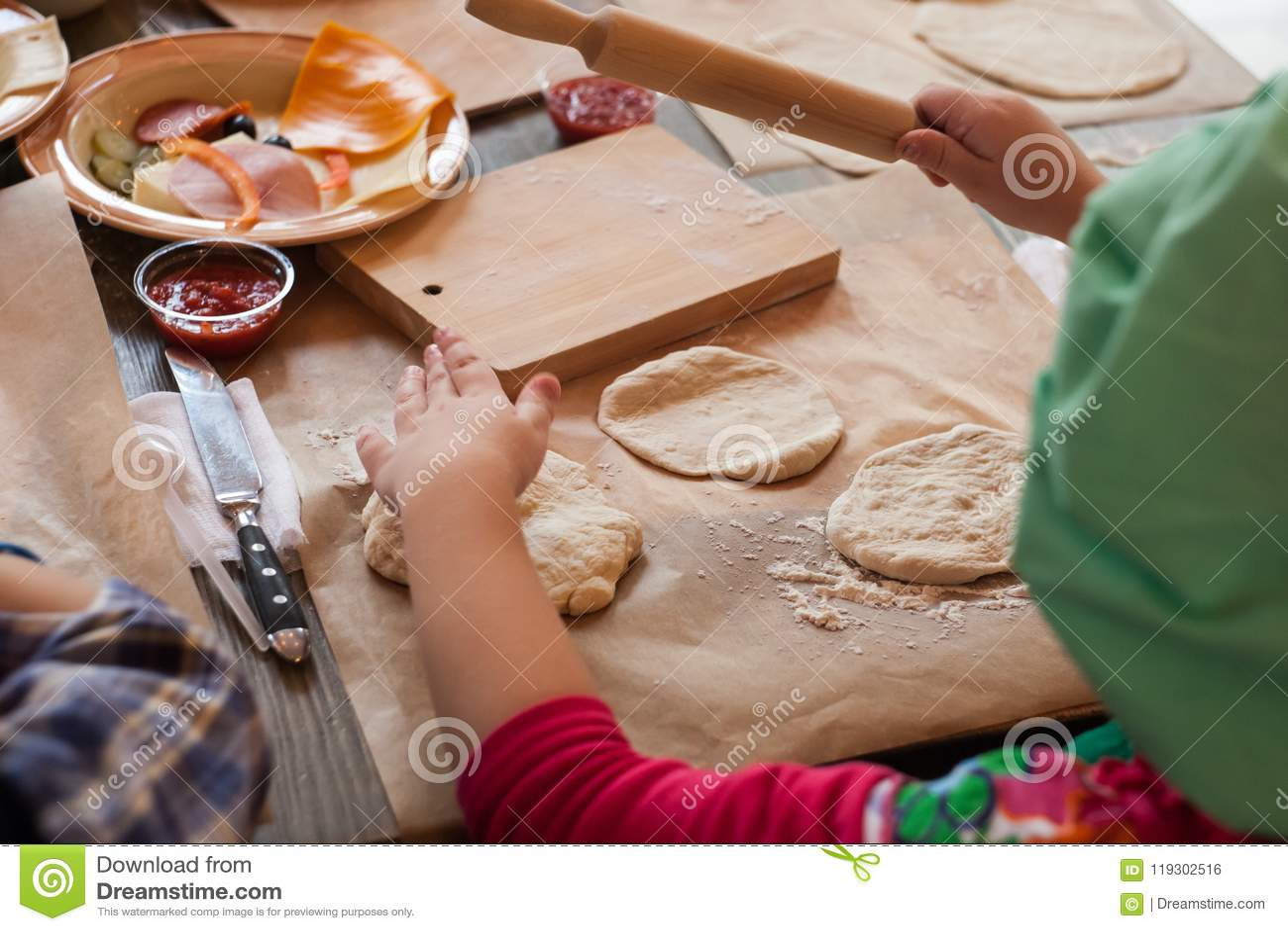 Мастерский класс для детей на печь смешную пиццу хеллоуина Маленькие ребеята учат сварить смешную пиццу изверга Дети подготавлива