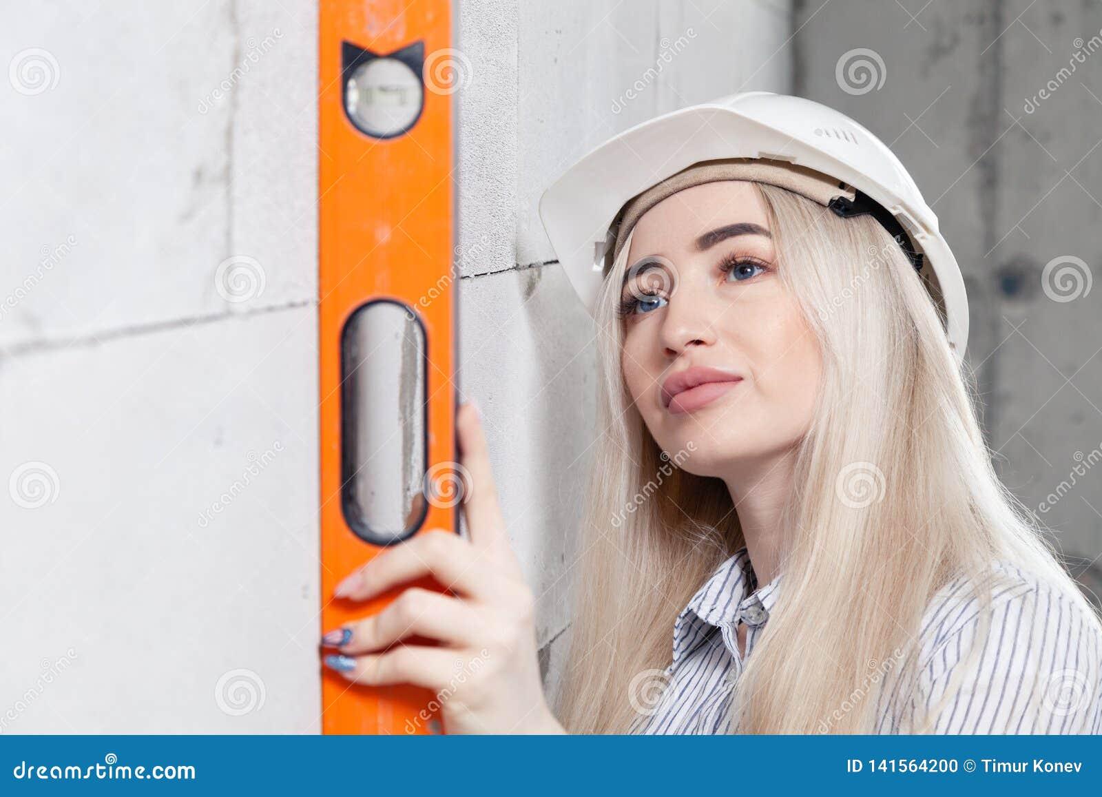 Мастер белокурой девушки крупного плана дизайнерский в белом шлеме конструкции измеряет уровень здания серого osibit стены оранже