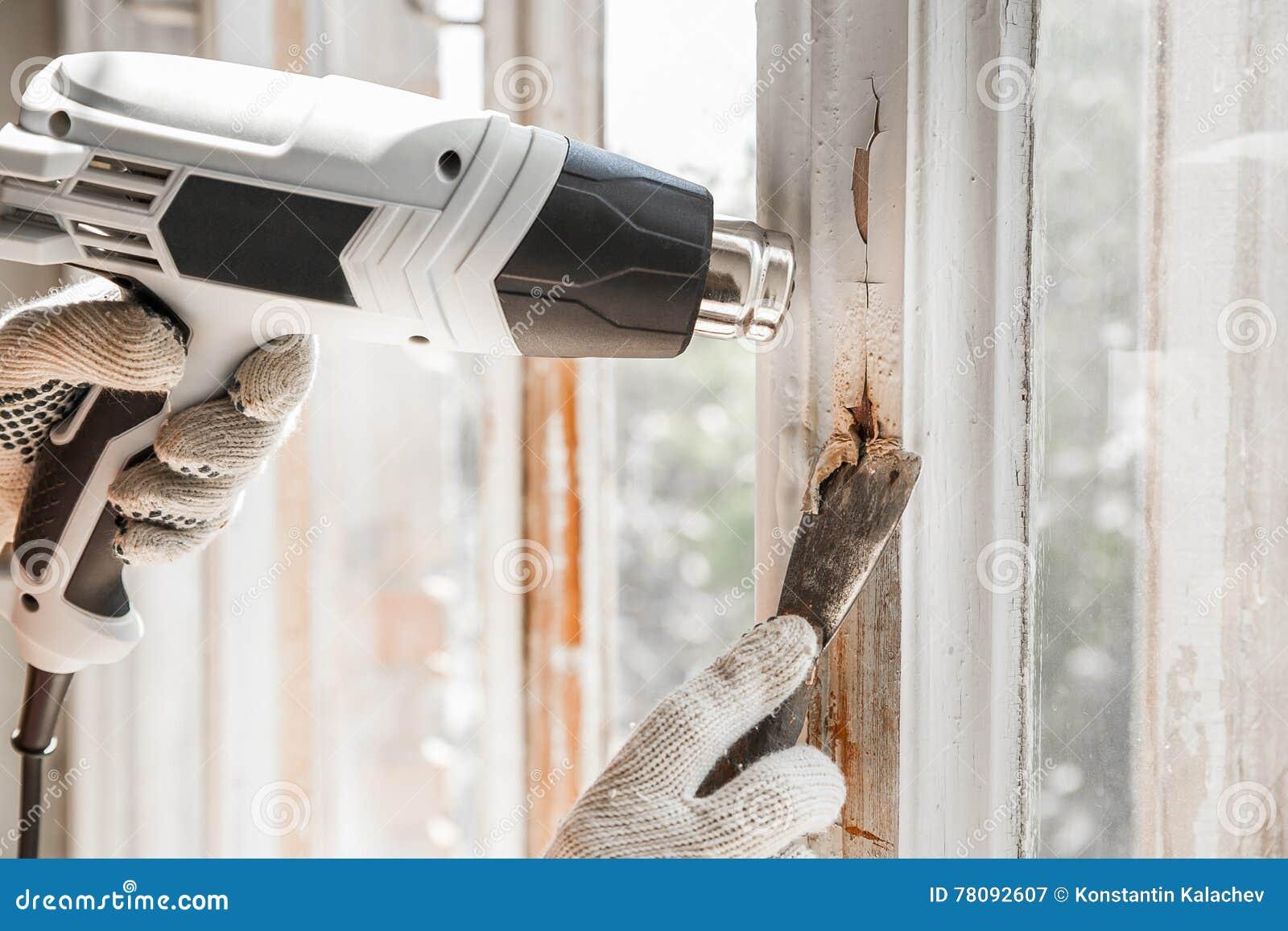 Мастер извлекает старую краску от окна с оружием и шабером жары closeup