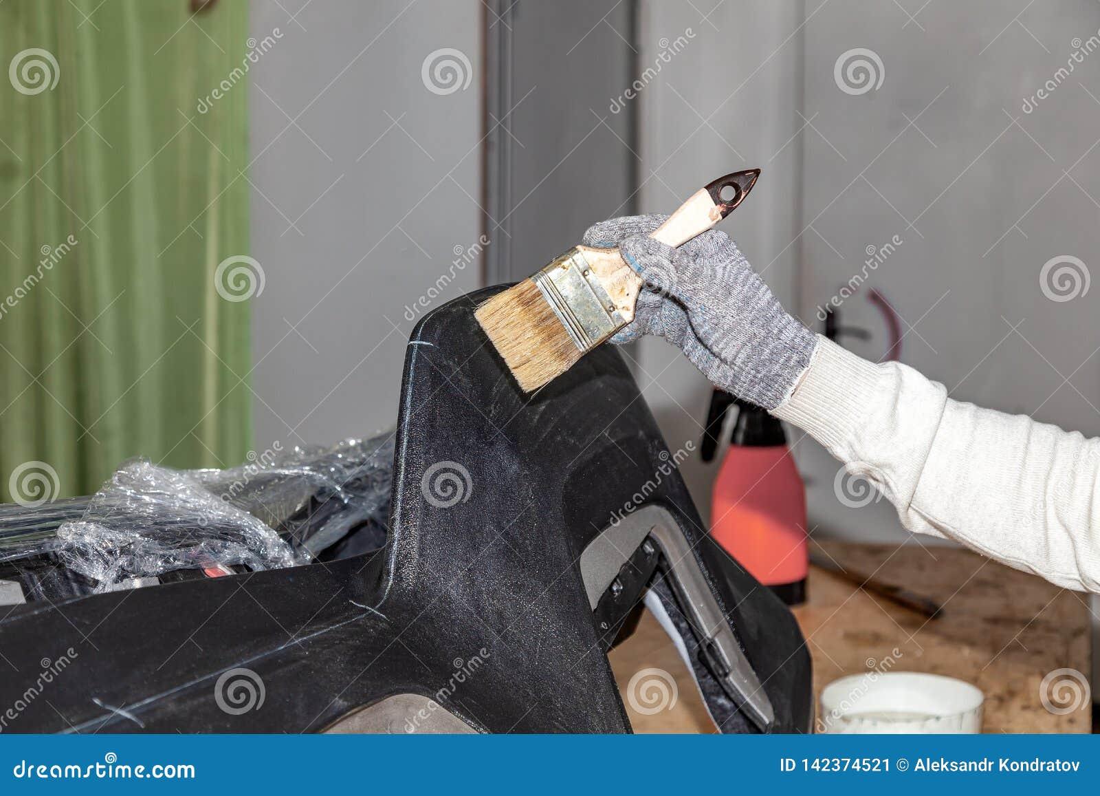 Мастер талии автомобиля прикладывая клей с щеткой на верхней пластиковой панели для вставки кожи в мастерской дизайна