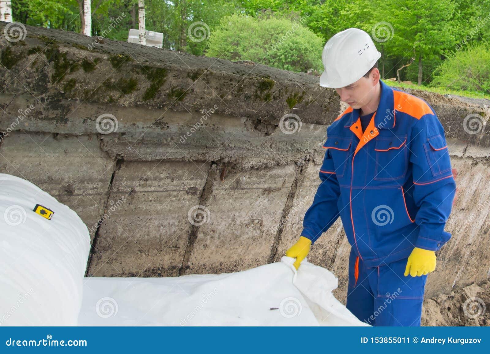 Материал для защиты поверхности почвы, разматывая работника в голубой форме и белого шлема на строительной площадке