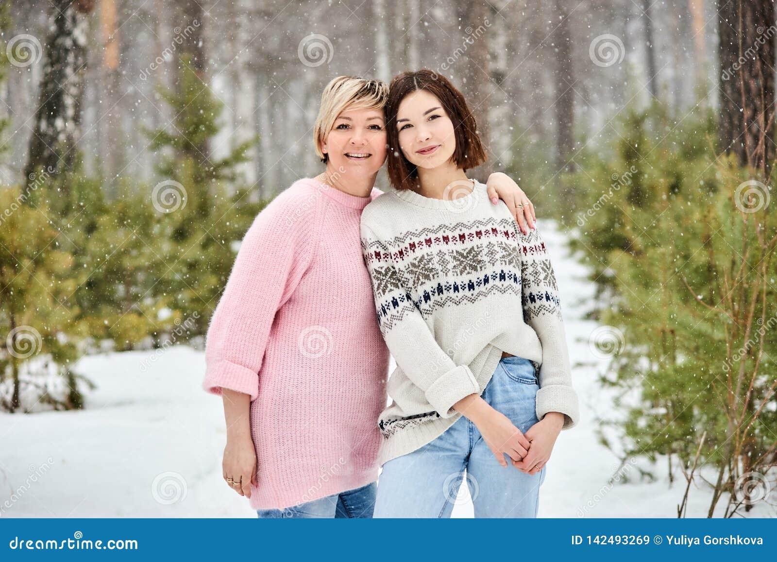 Мать и взрослая дочь идя в снежности леса зимы