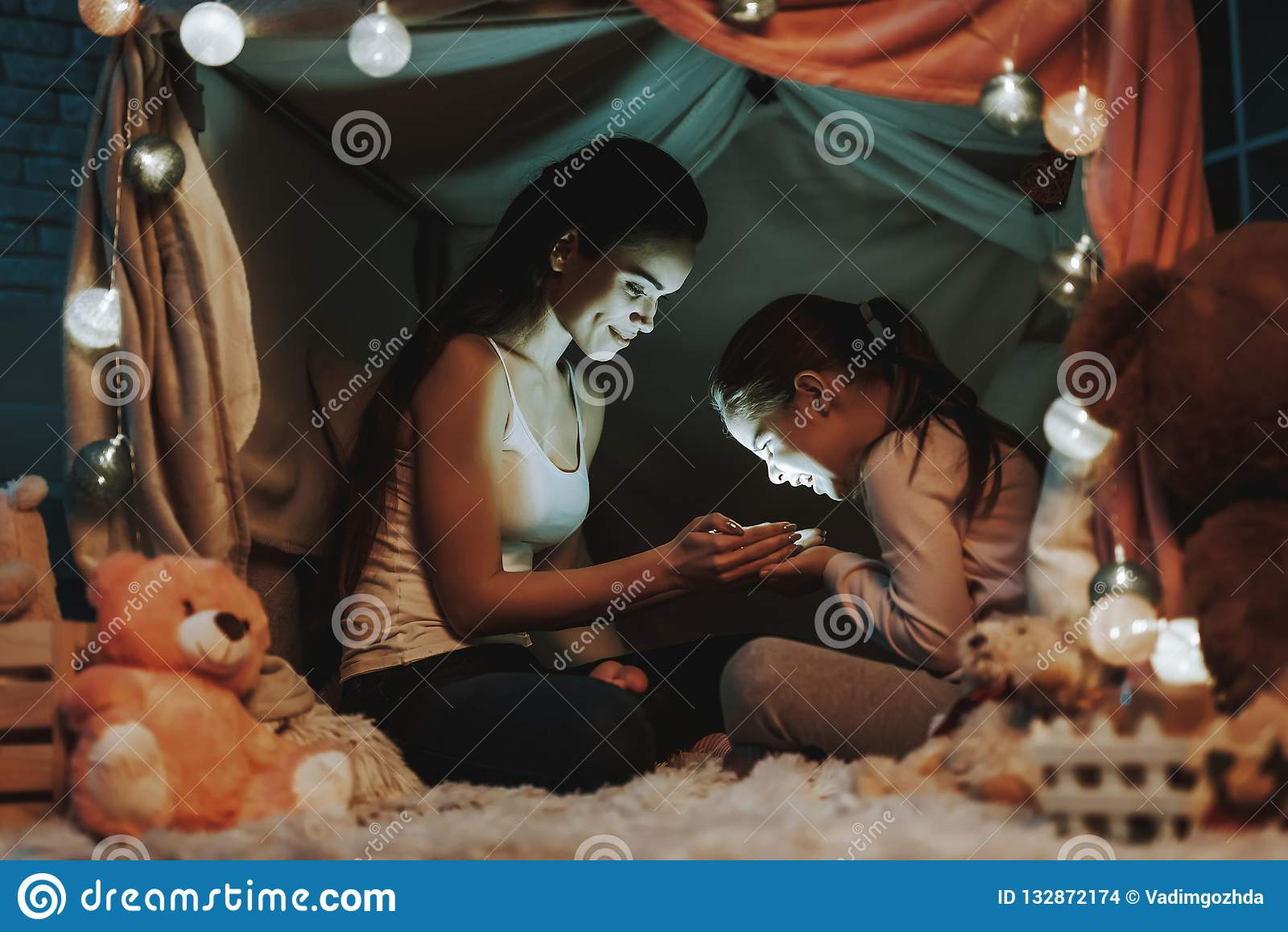 Мать и дочь держат свет в руках