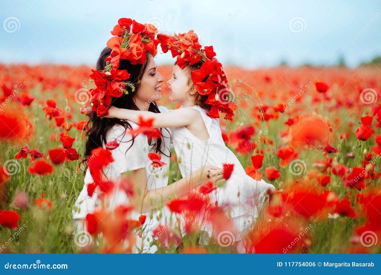 Мать и дочь играя в поле цветка