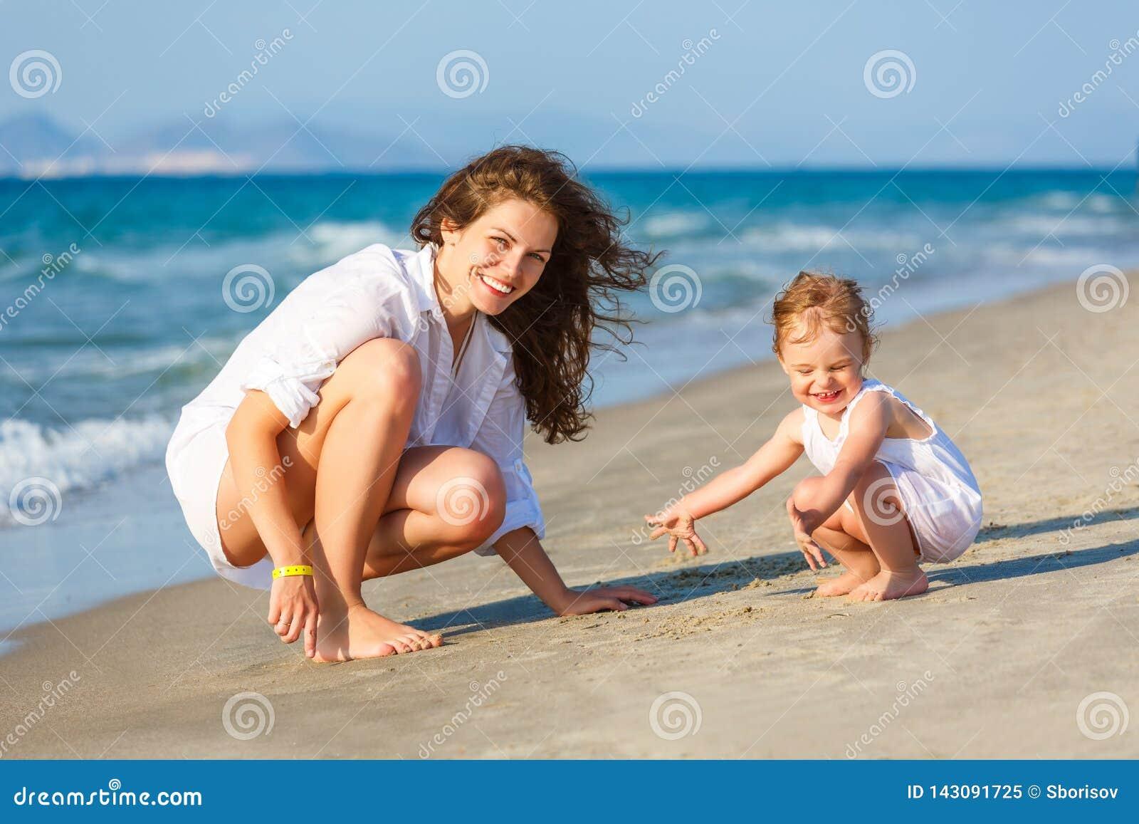 Мать и дочь играя на пляже моря в Греции