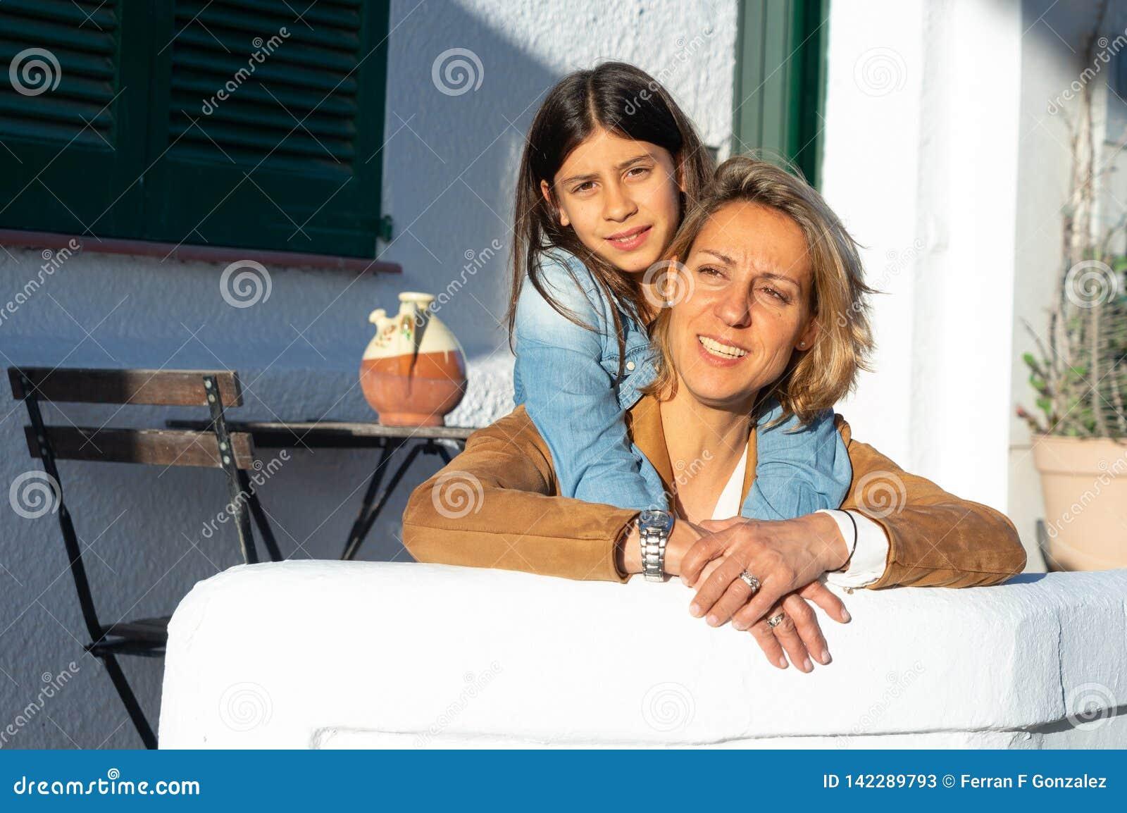 Мать и дочь обняли в заходе солнца в среднеземноморской деревне с белыми стенами