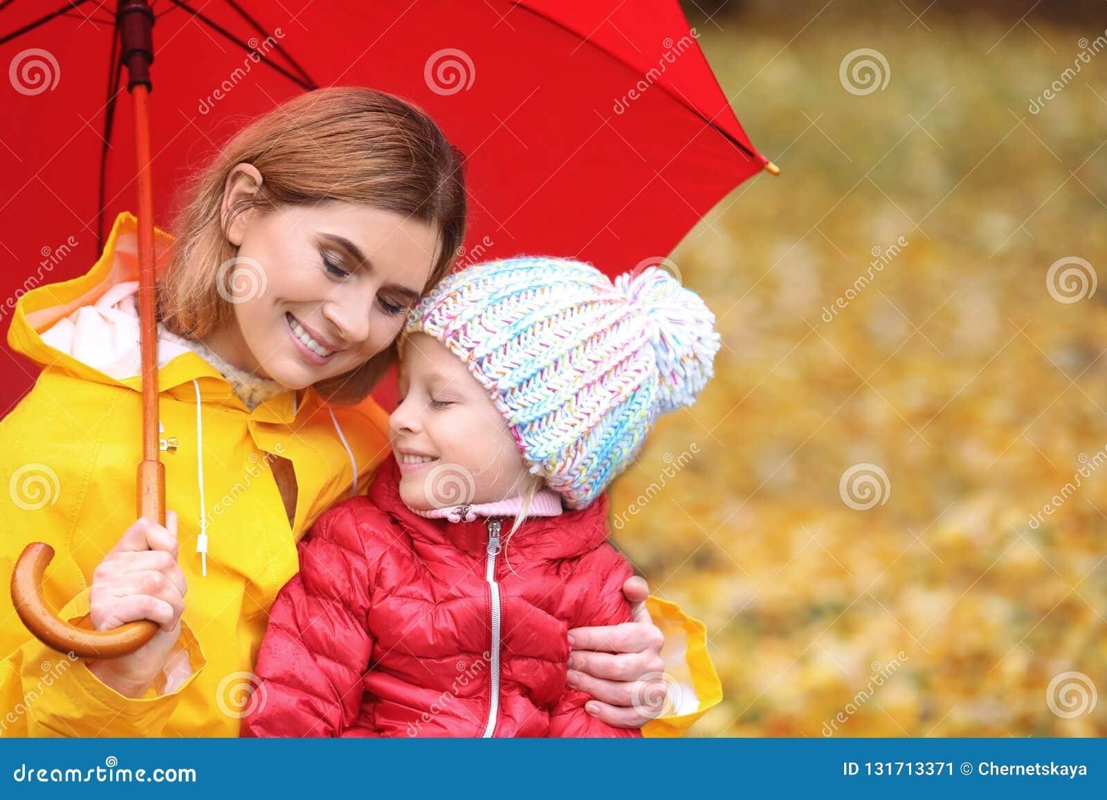 Мать и дочь с зонтиком в парке осени