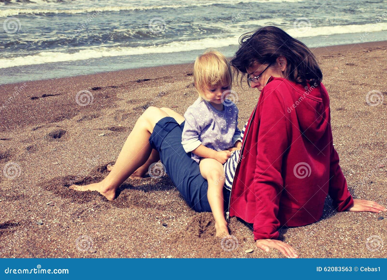 Мать и молодая дочь сидя на пляже