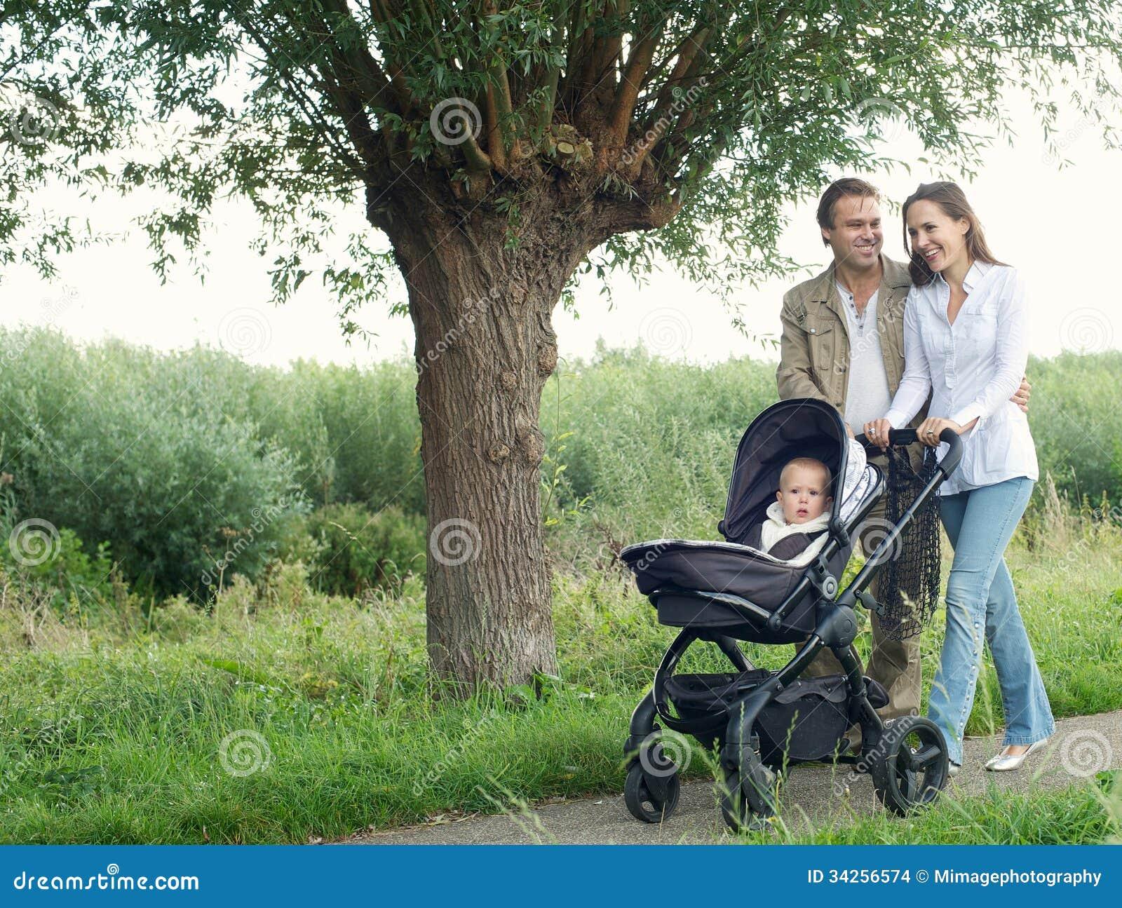 Мать и отец идя outdoors и нажимая младенца в pram