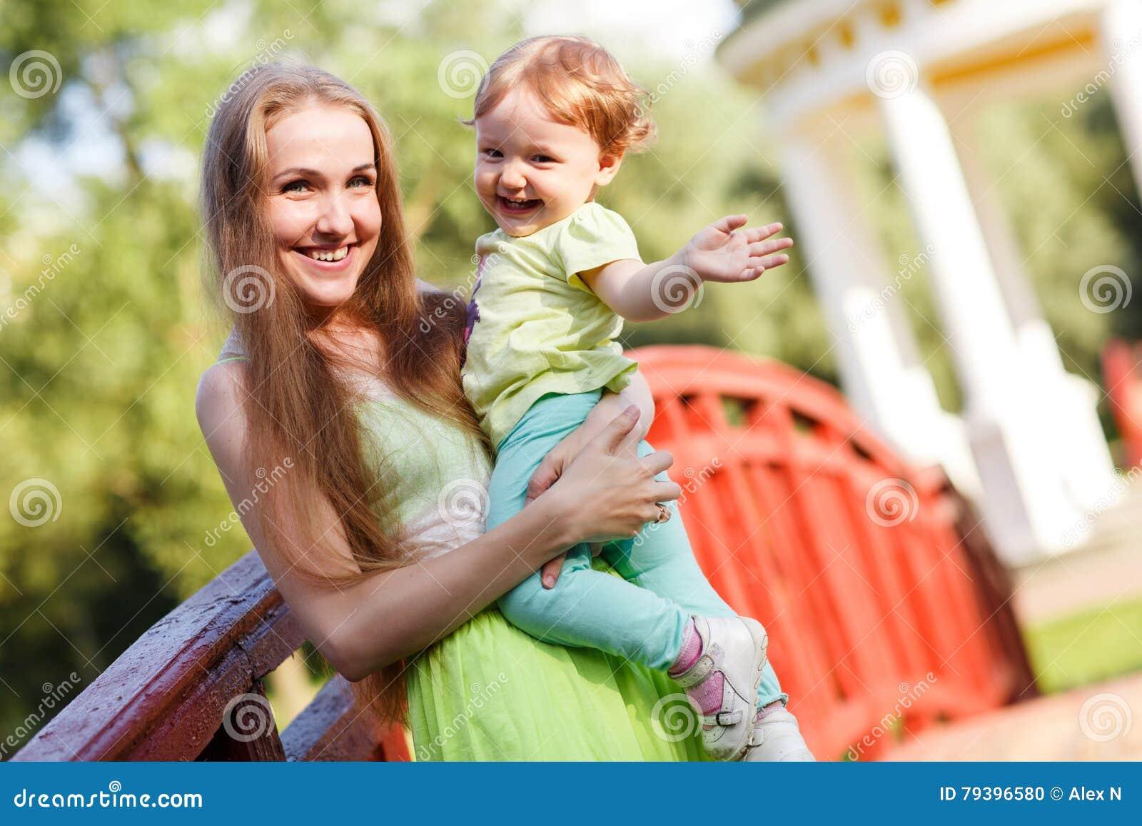 Мать и дочь потехи в парке на мосте