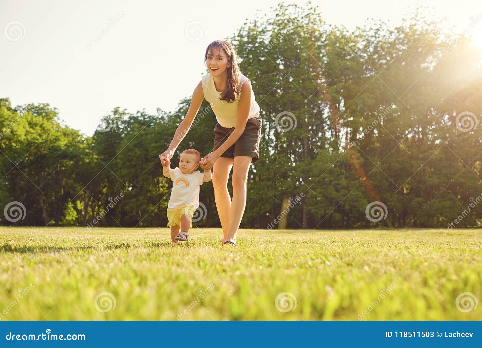 Мать и ребенок идут в парк на заходе солнца