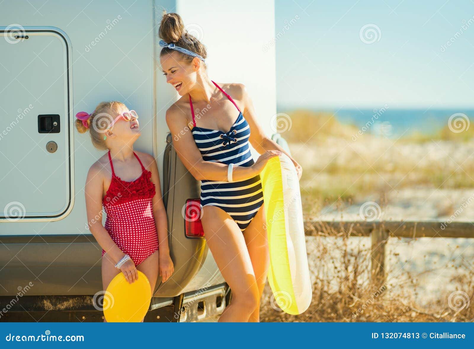 Мать и ребенок с желтое раздувное lifebuoy смотрящ каждое