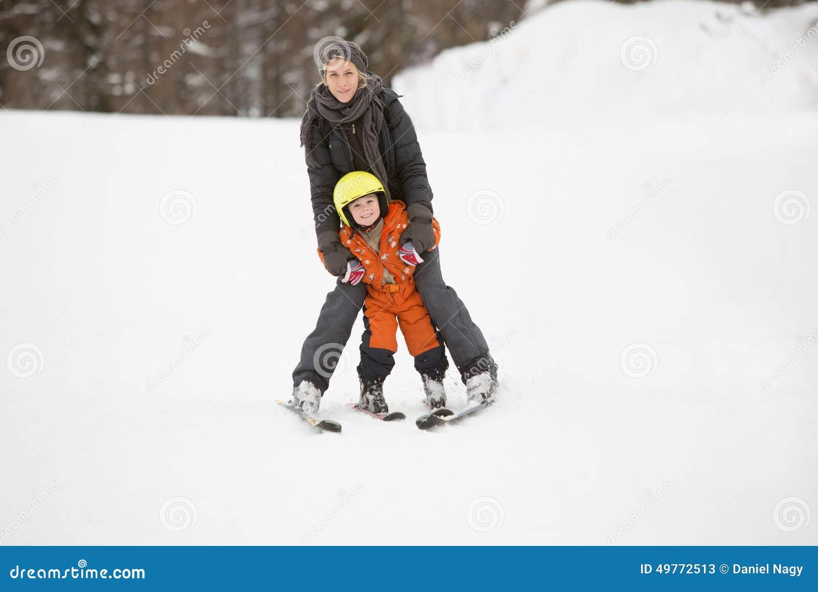Мать и ребенок учат кататься на лыжах совместно