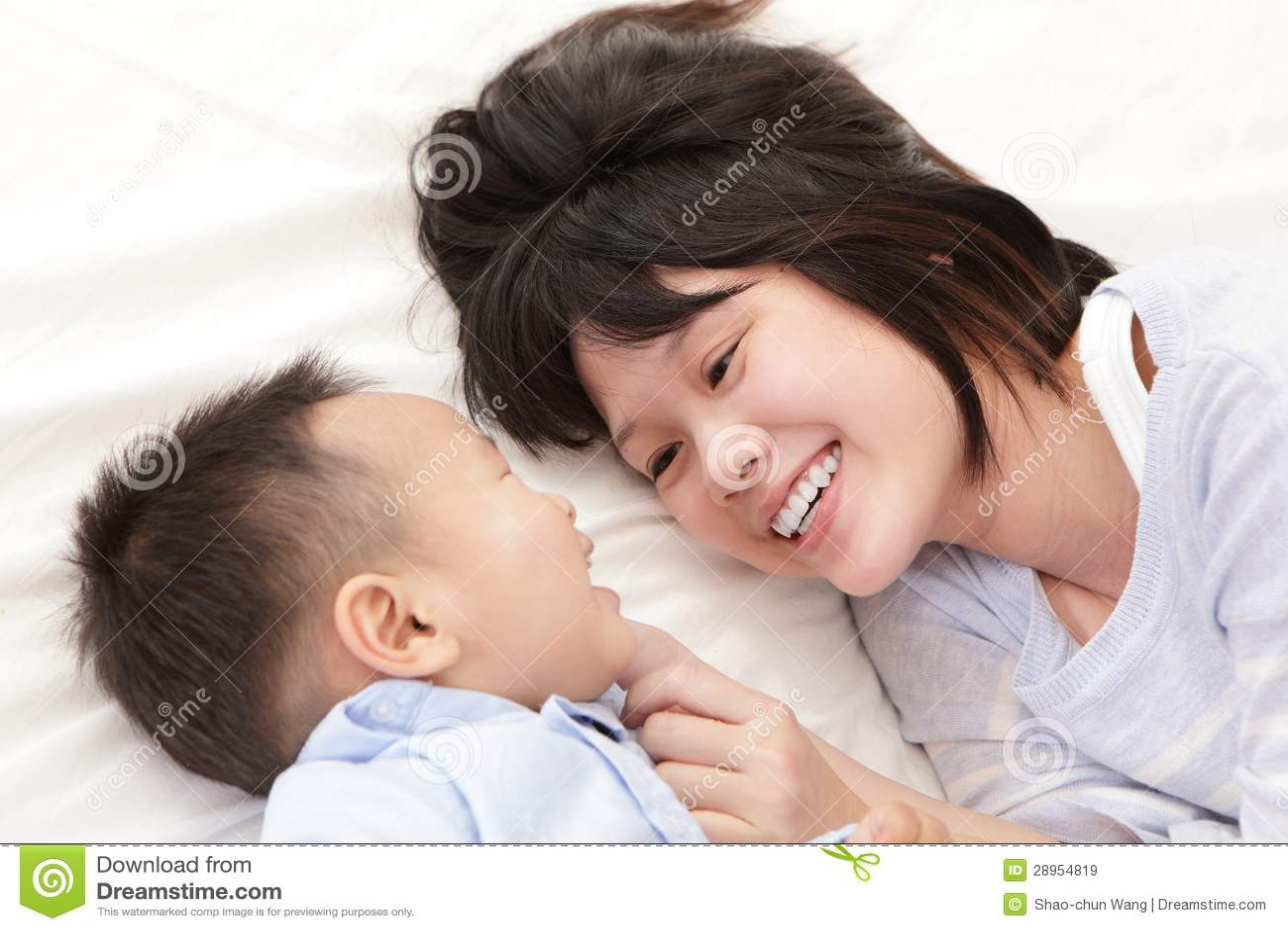 Мать и сынок усмедутся и смотрятся один другого