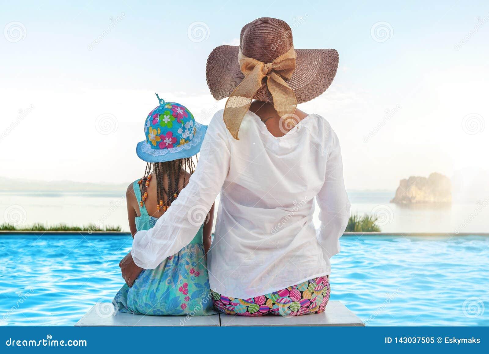 Мать и daugher сидя на пейзажном бассейне