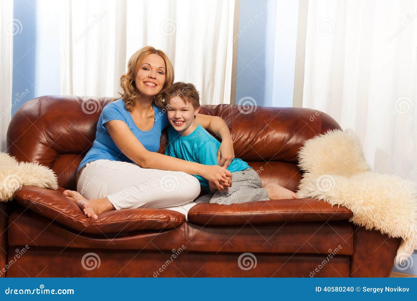 Мать обнимает ребенка сидя на кресле дома