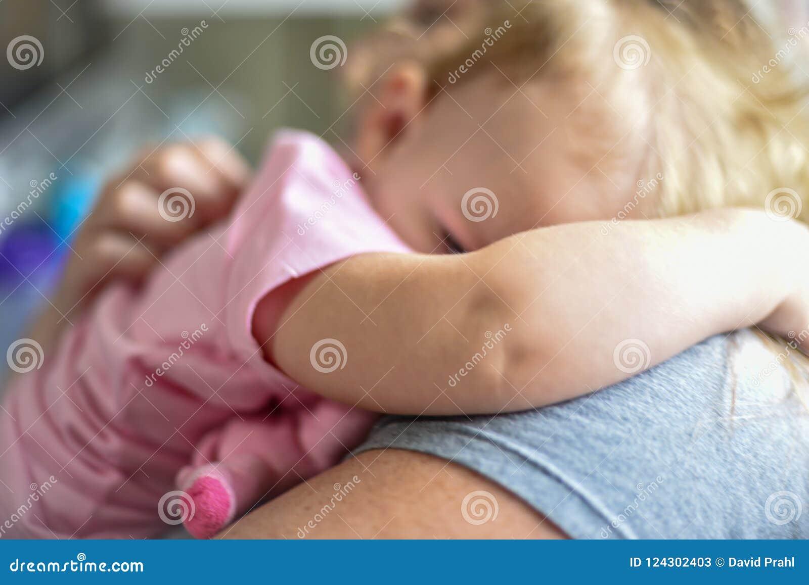 Мать обнимая ребенка в солнечном свете