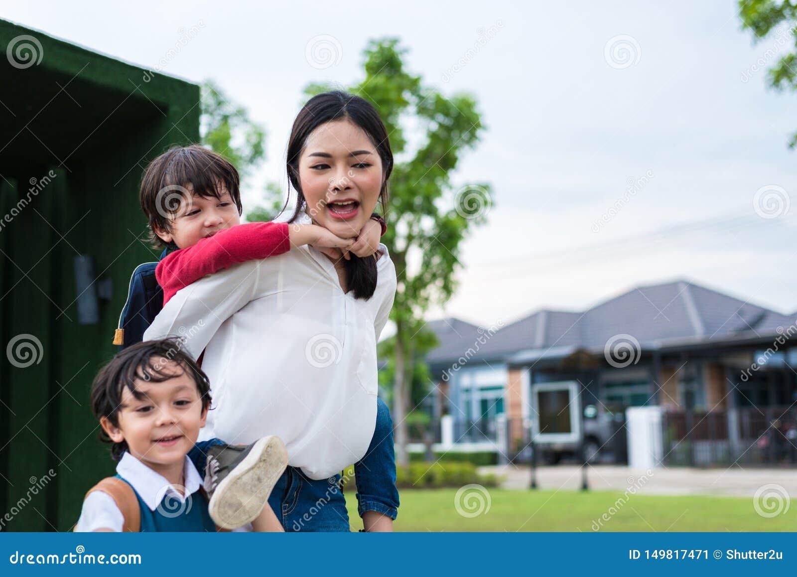Мать-одиночка нося и играя с ее детьми в саде с зеленой предпосылкой стены Концепция людей и образов жизни t