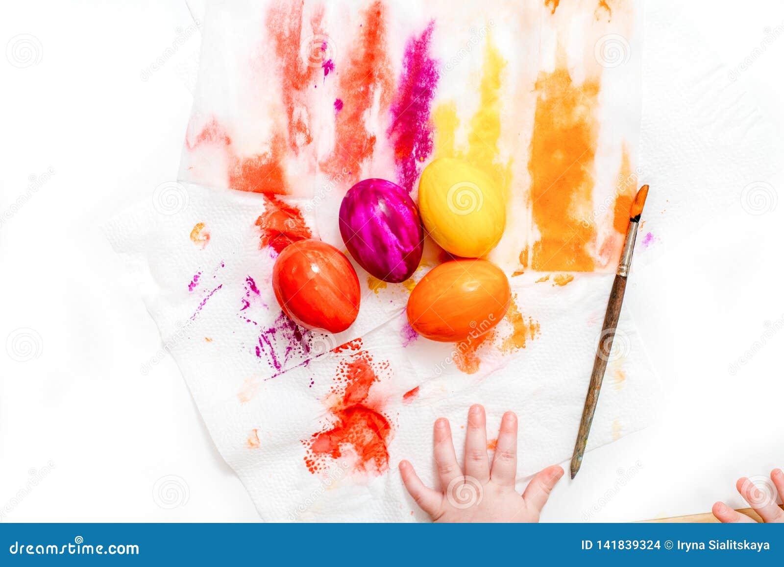 Мать, отец и сын красят яйца r
