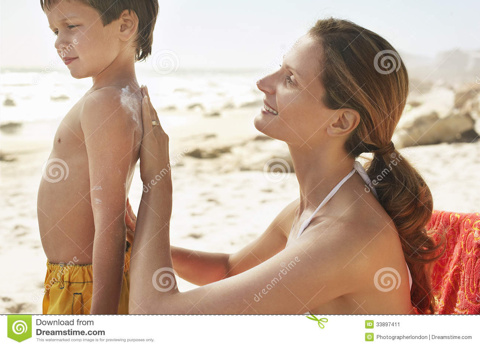 Мать прикладывая сливк солнцезащитного крема на задней части сына