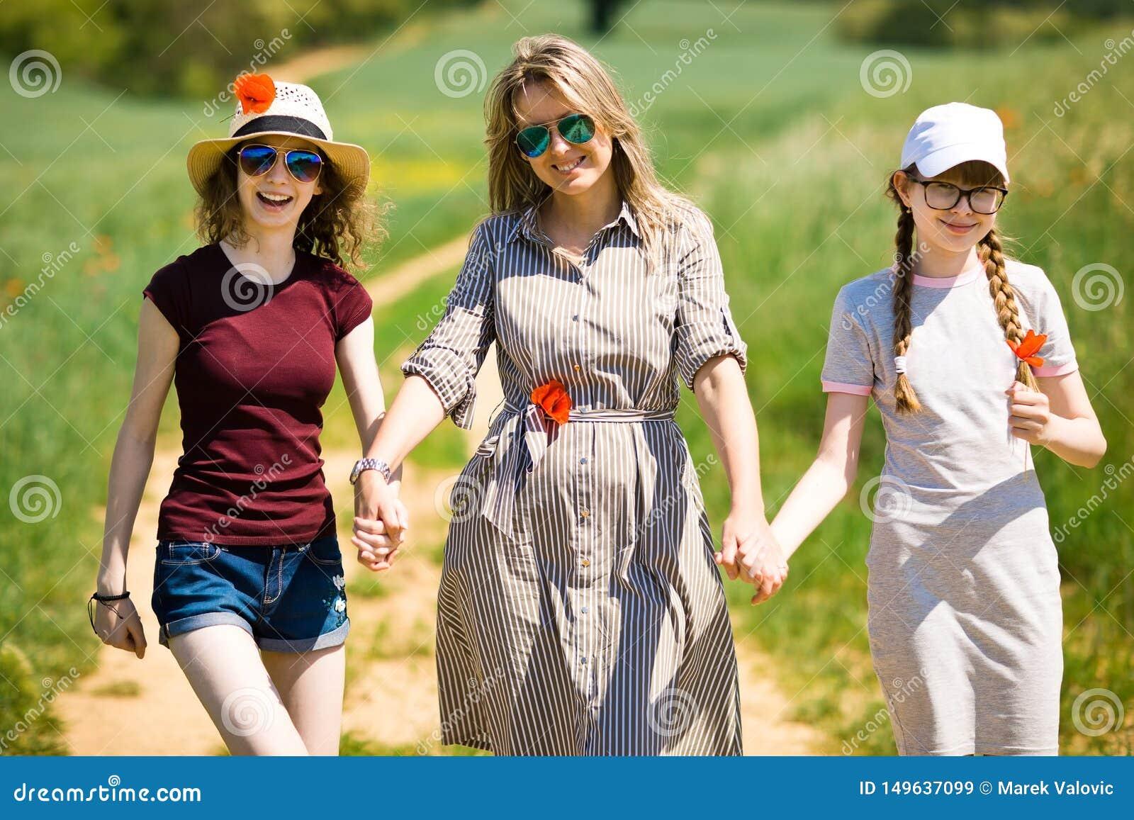 Мать с дочерью имея цветки мака идет на дорогу тележки