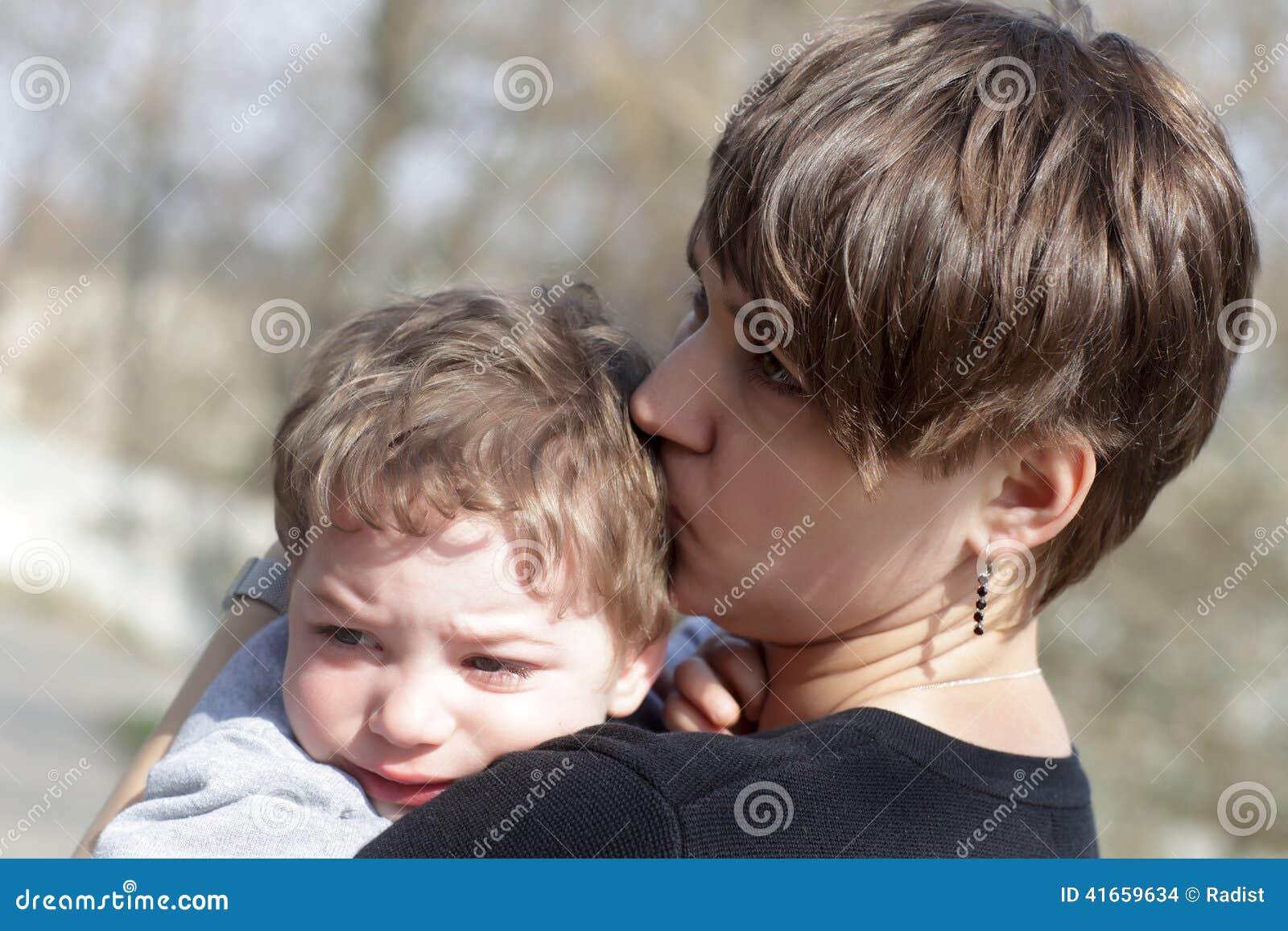 Мать целуя ее плача сына