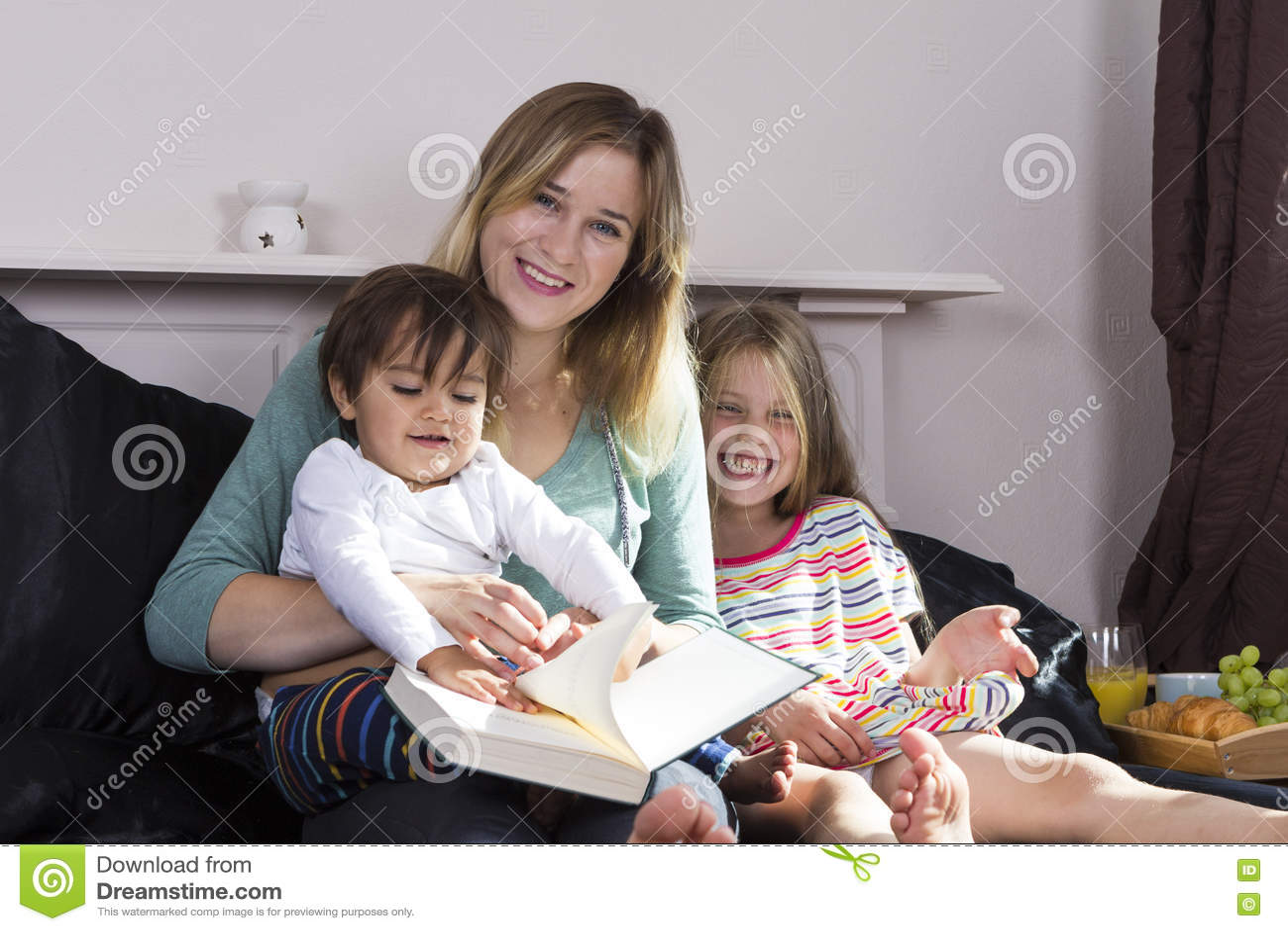 Мать читая к детям в кровати
