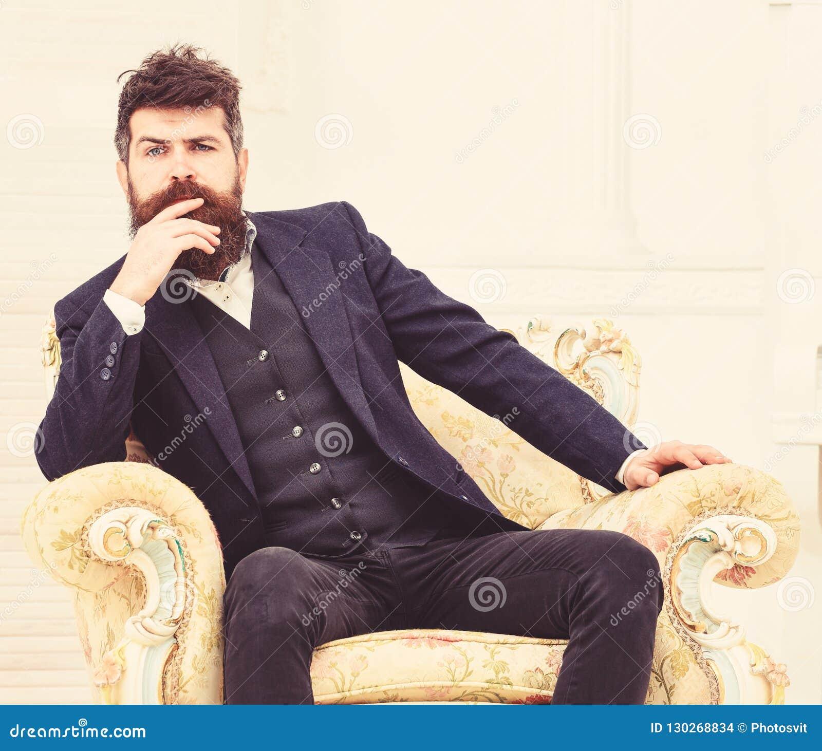 Мачо привлекательное и элегантный на серьезной стороне и заботливом выражении Человек с бородой и усик нося классический костюм