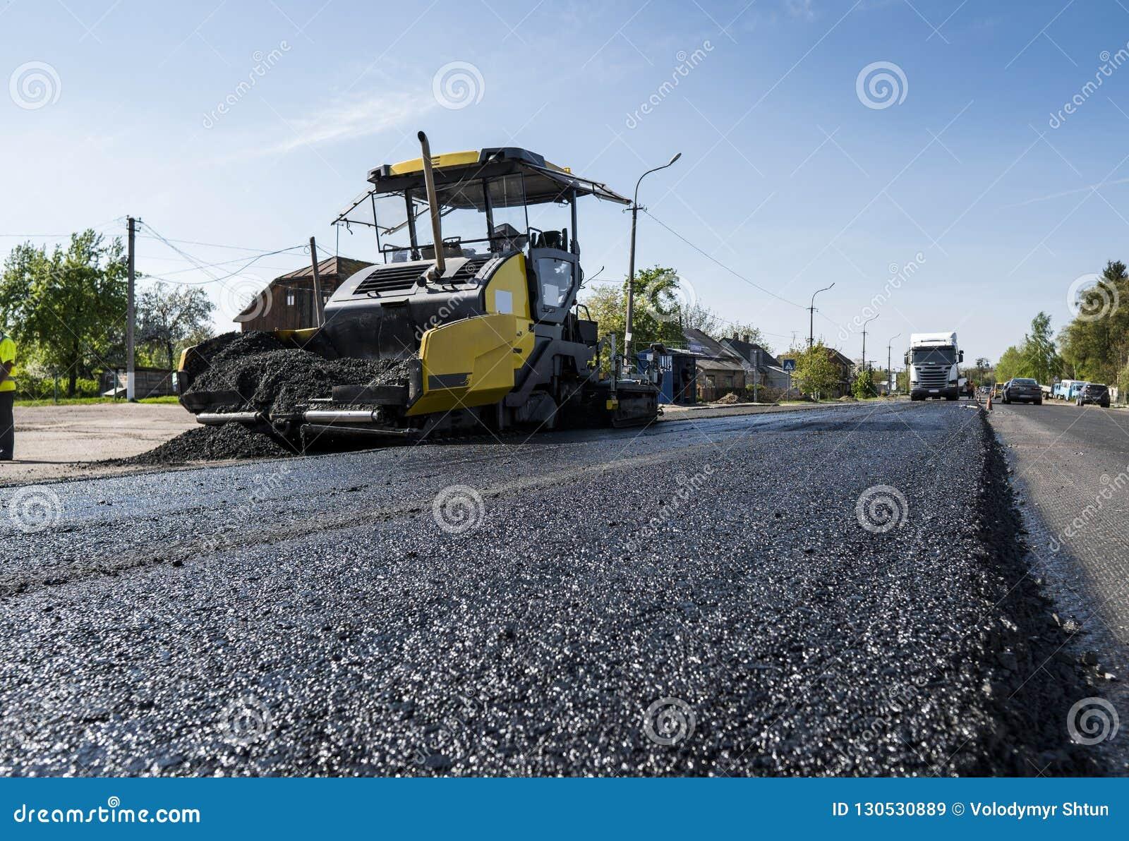Машина paver асфальта работника работая во время строительства дорог и ремонтировать работает Фертиг-аппарат paver, фертиг-аппара