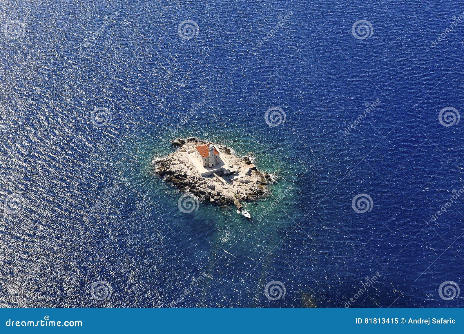 Маяк на малом утесе окруженном с морем сверху