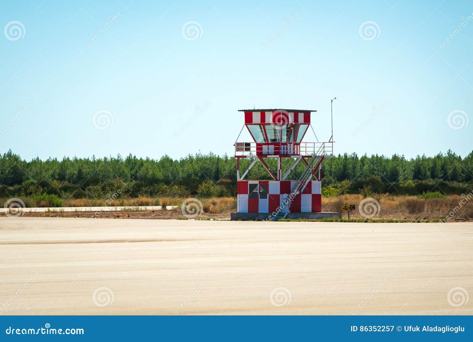 Малая красная и белая башня авиадиспетчерской службы рядом с пустым взлётно-посадочная дорожка авиапорта Зеленые поля и голубое н
