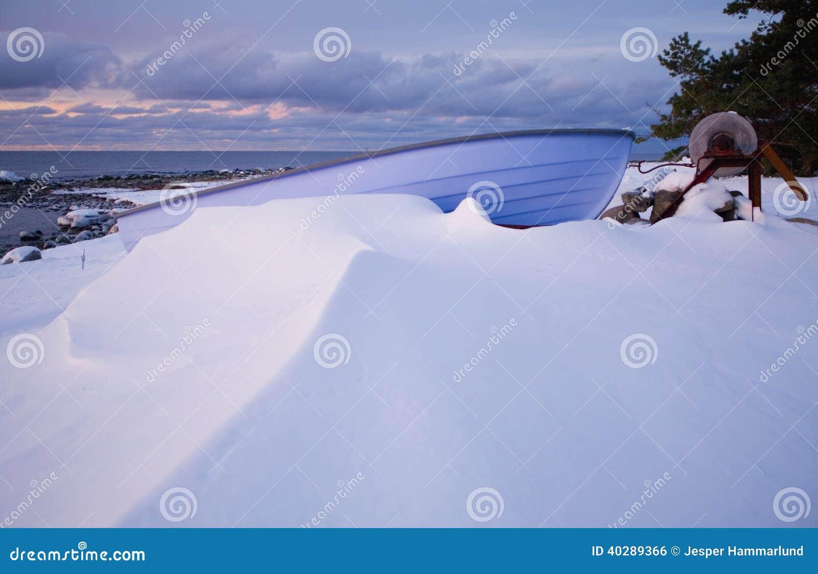 Малая шлюпка строки кладя на Pebble Beach предусматриванное в снеге