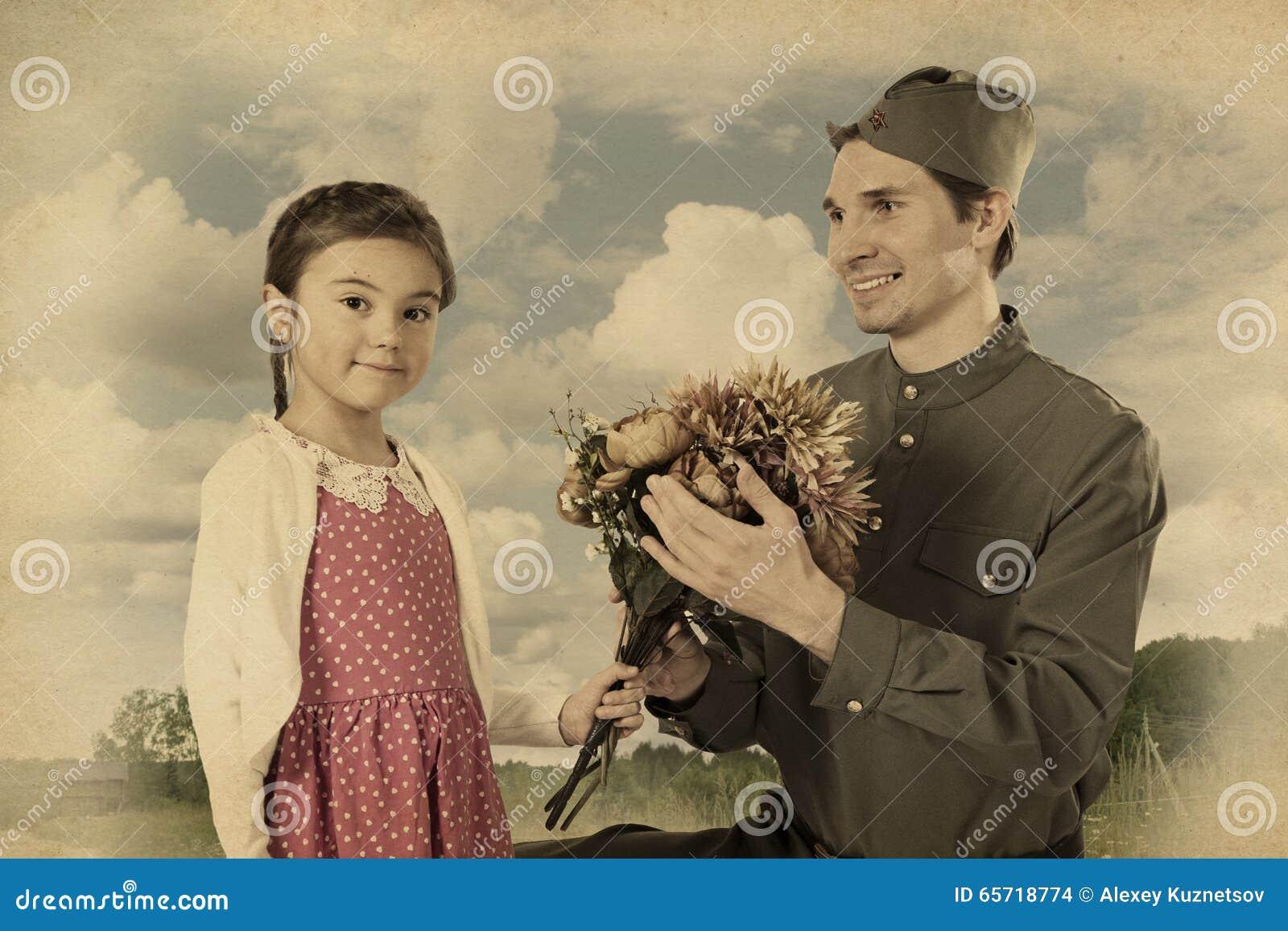 Маленькая девочка давая пук цветков к советскому солдату