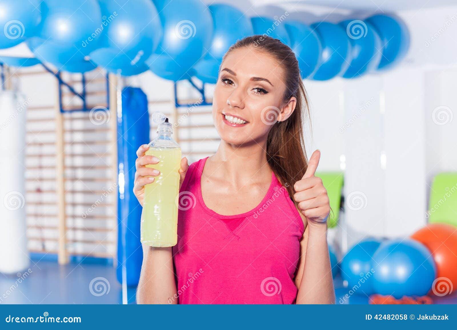 Маленькая девочка выпивая изотонное питье, спортзал Она счастливый и полный o