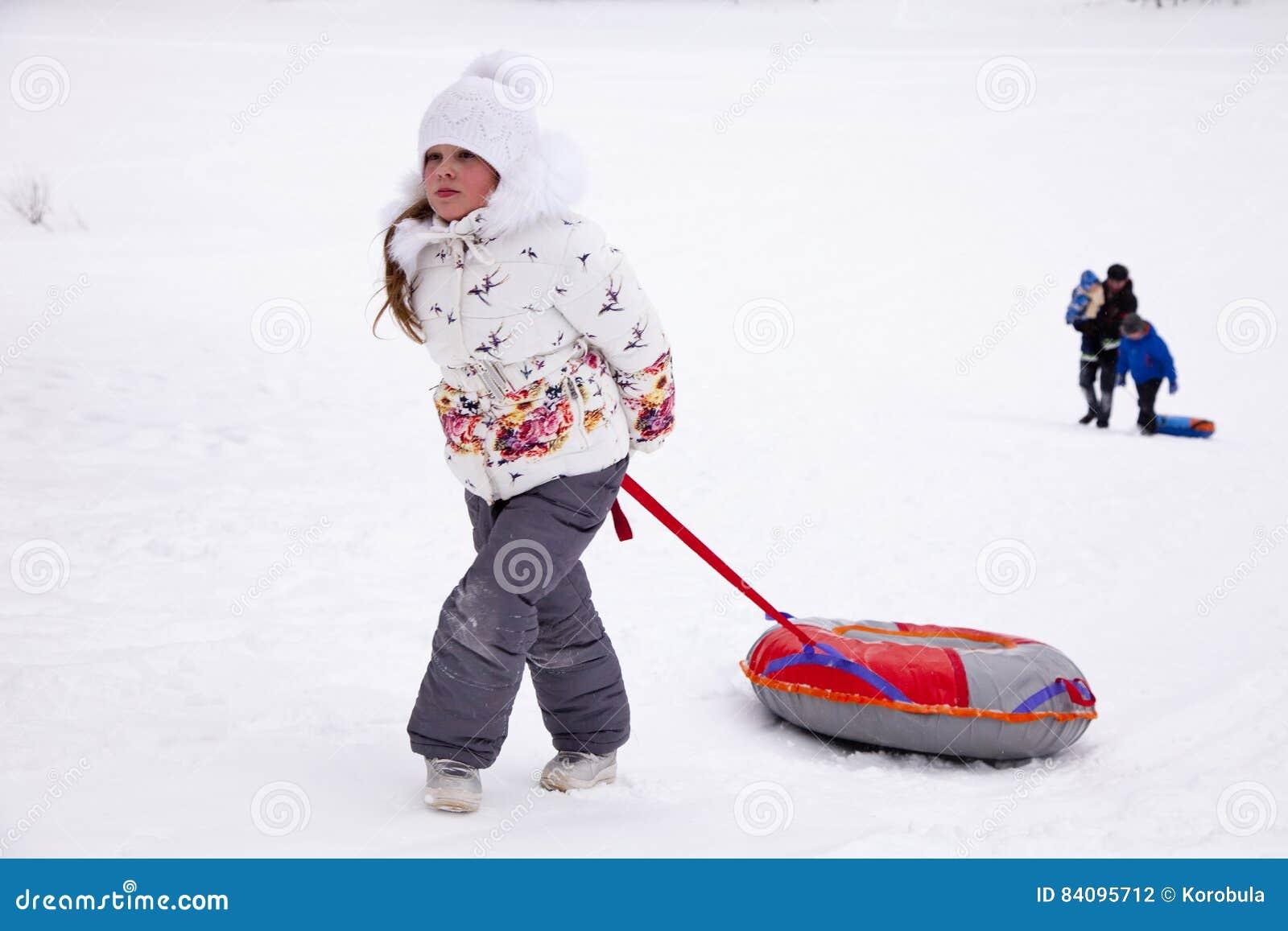 Маленькая девочка вытягивая трубопровод снега ремня