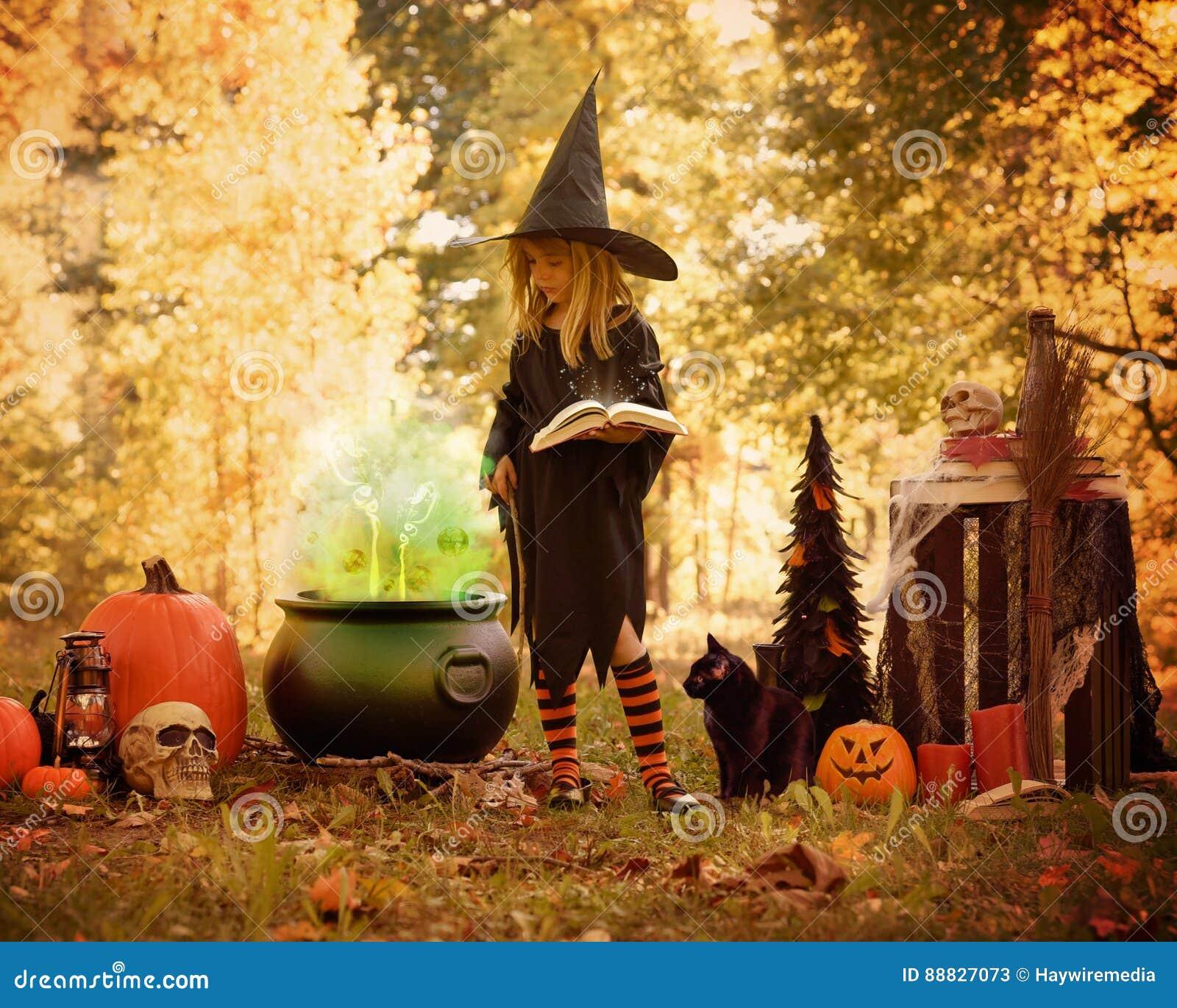Маленькая девочка в костюме ведьмы снаружи с волшебной книгой