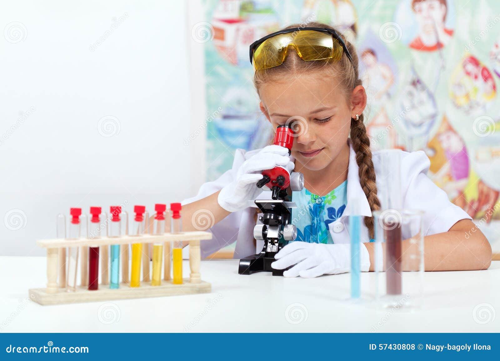 Маленькая девочка в классе науки используя микроскоп