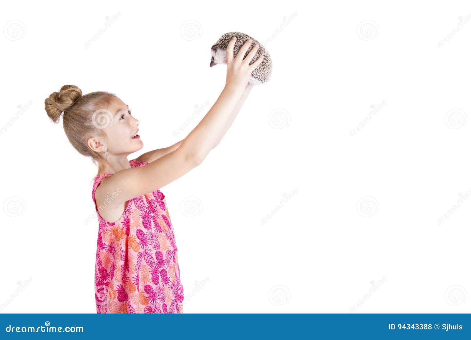 Маленькая девочка держа ее ежа любимчика вверх в воздухе