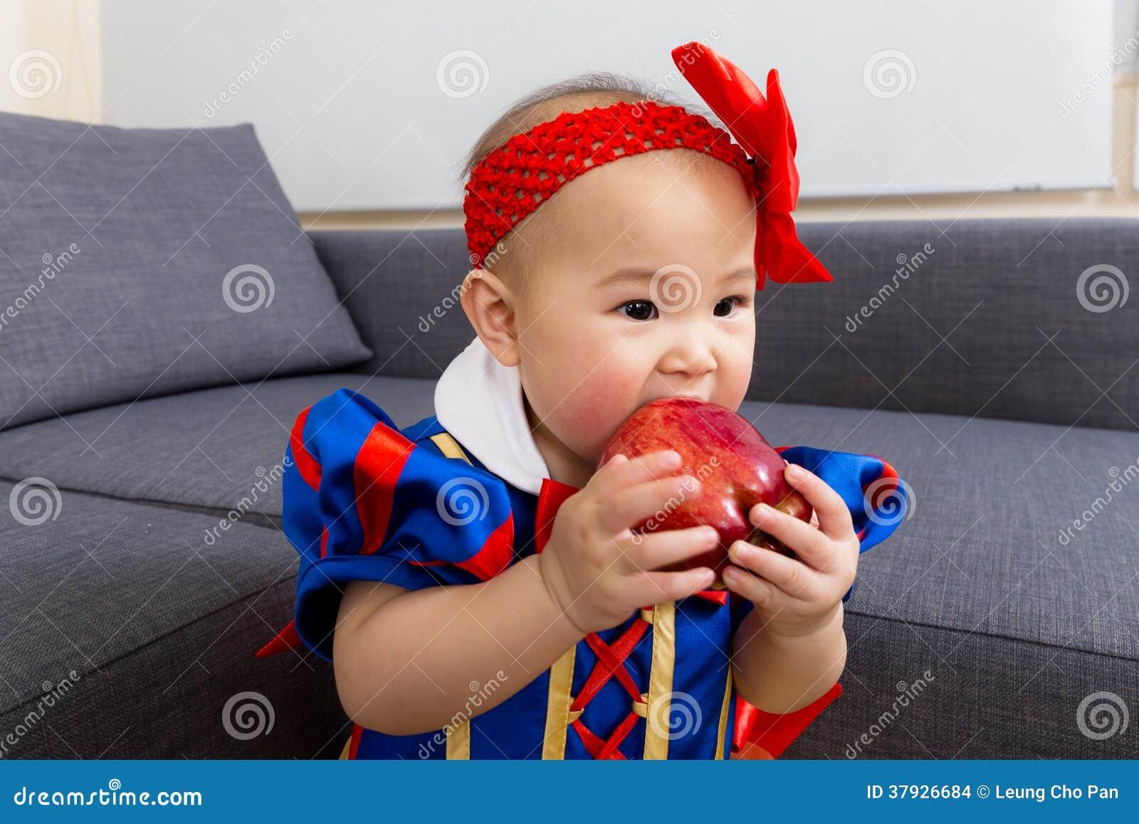 Маленькая девочка ест яблоко