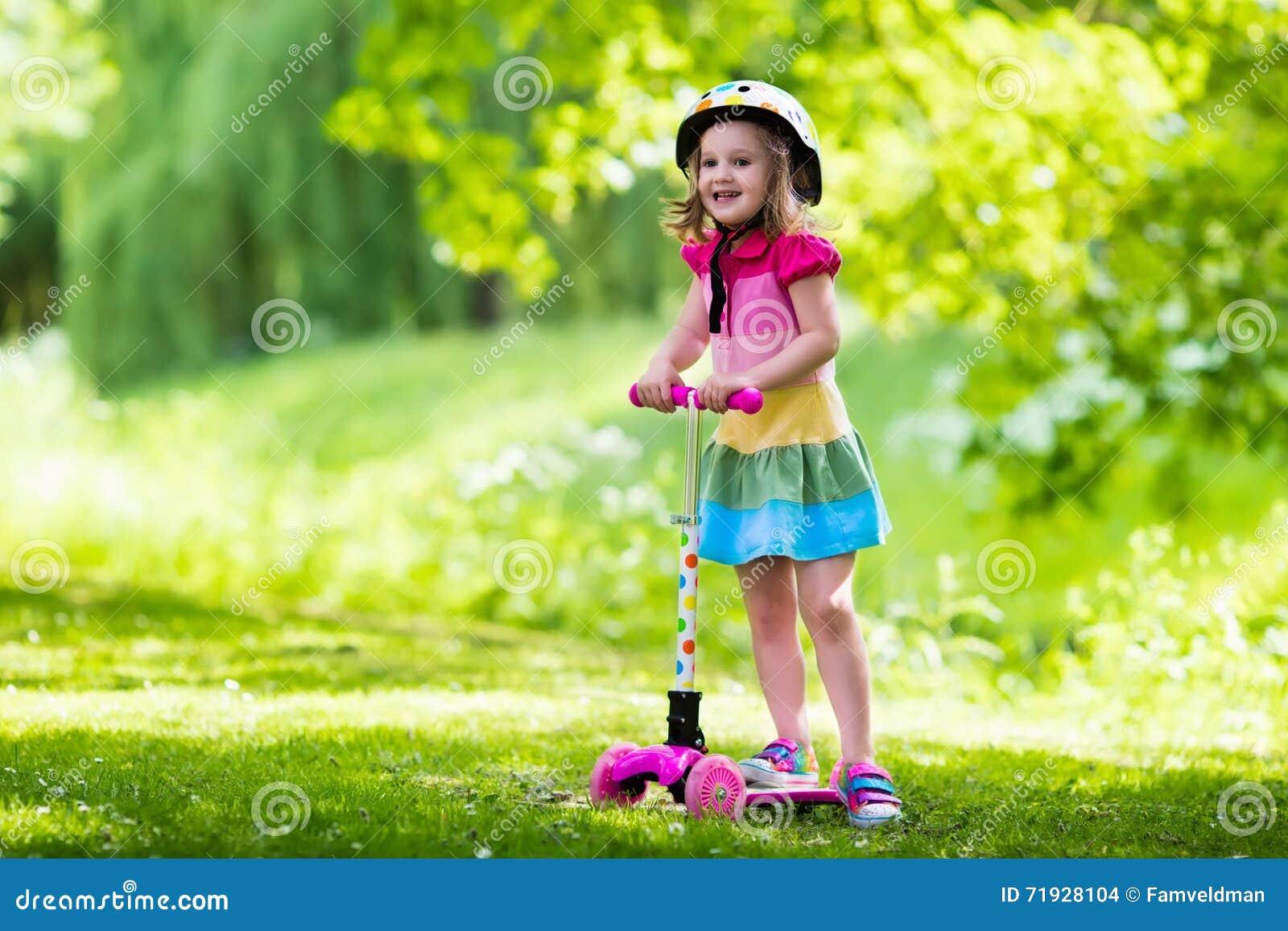 Маленькая девочка ехать красочный самокат