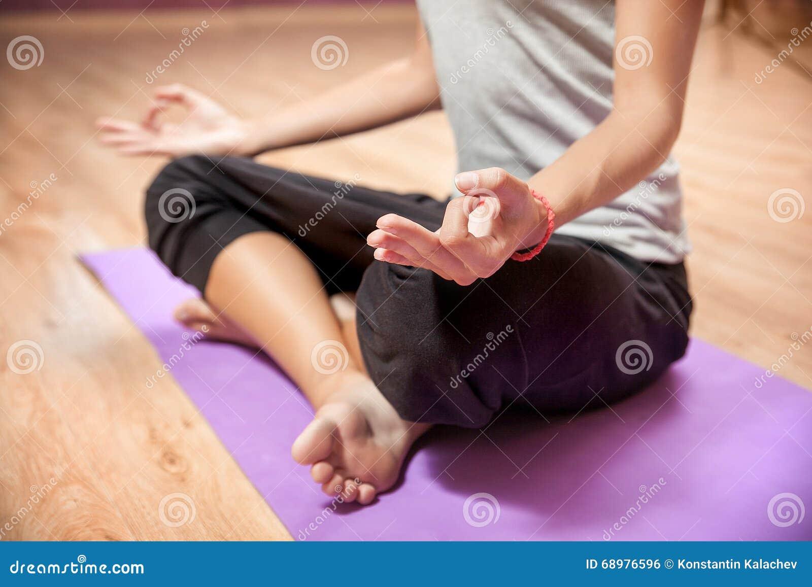 Маленькая девочка делая йогу в крупном плане положения лотоса внутри помещения
