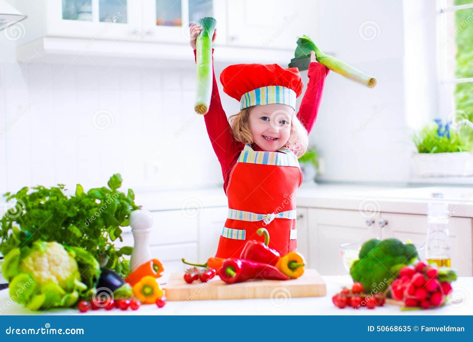 Маленькая девочка делая салат для обедающего