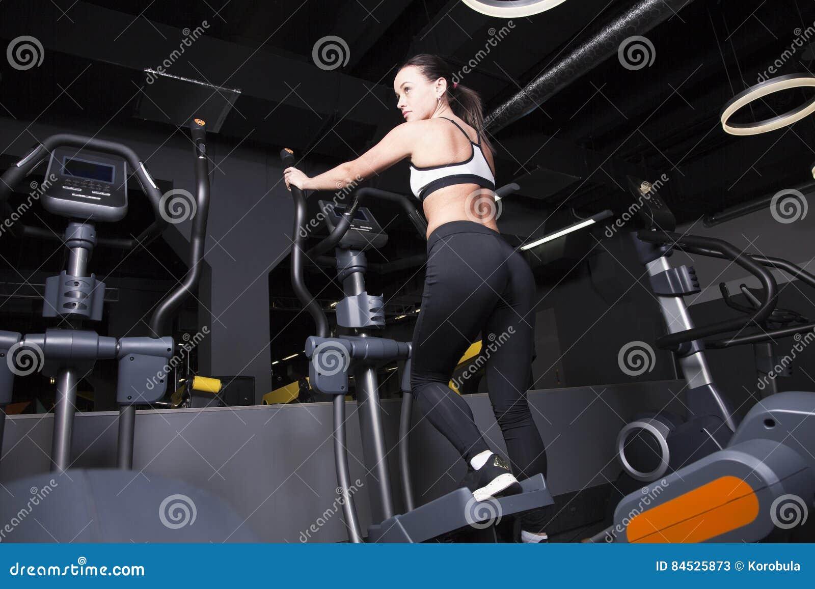 Маленькая девочка идет внутри для спорт в спортзале